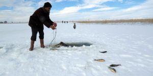Balıkçılar donan goldeki buzları motorlu testereyle kesip avlanıyor
