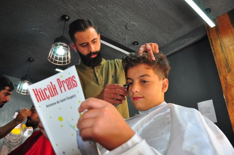 Kitap okuyan çocukları ücretsiz tıraş ediyor